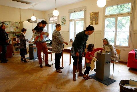 Sveits har holdt verdens første folkeavstemning om borgerlønn. Her i et stemmelokale på en skole i Bern søndag.