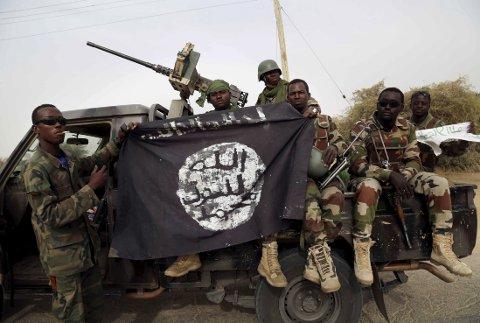 NIGERIA: Boko Haram har skapt ustabilitet og frykt nord i Nigeria og i nabolandene rundt. Her holder nigerianske sopldater opp et flagg de har tatt fra Boko Haram.