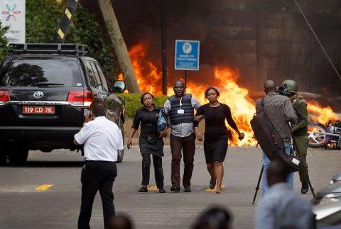 Sikkerhetsstyrker hjelper sivile med å flykte under angrepet i Nairobi i Kenya tirsdag.