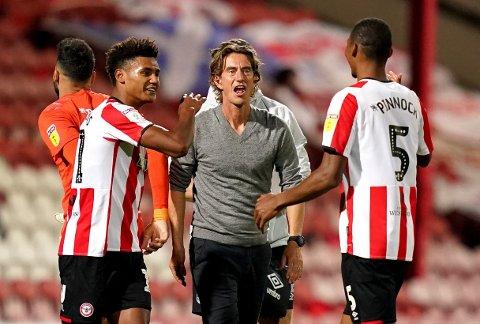 Brentford-manager Thomas Frank (midten) feirer at de er i playoff-finalen sammen med Ollie Watkins (t.v.) og Ethan Pinnock etter at de slo Swansea påGriffin Park.