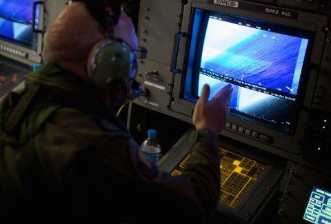SØKER: Et besetningsmedlem ombord på australske AP-3C Orion-fly ser på en skjerm i jakten på deler fra det forsvunnede flyet fra Malaysia Airlines.