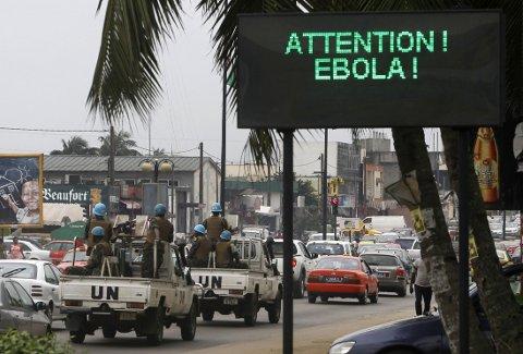 En FN-kolonne med soldater kjører forbi et skilt som advarer om smittefaren i Abidjan på Elfenbenskysten.