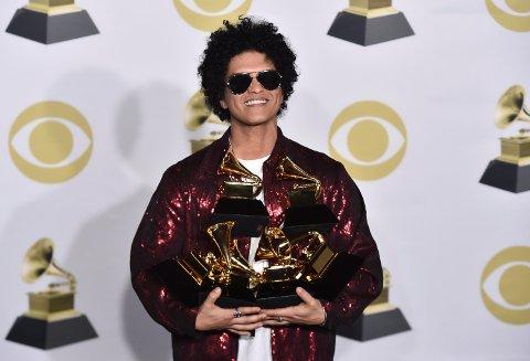 Bruno Mars poserer med Grammy-prisene han vant for blant annet årets låt og årets album - totalt hele syv stykker.