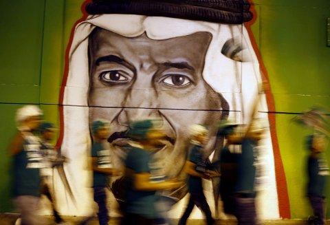 IKKE-GIFTE FÅR SOVE SAMMEN: Grunnen til endringen i loven er at Saudi-Arabia ønsker å øke inntektene fra turismen til 10 prosent av landets bruttonasjonalprodukt (BNP) innen 2030, opp fra dagens andel på 2 prosent. Illustrasjonsfoto: Folk på vandring forbi et veggmaleri av Saudi-Arabias kronprins Mohammad Bin Salman.