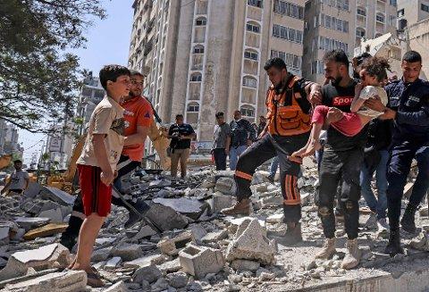 REDDES: Palestinere evakuerer en skadet jente fra ødelagte bygningsmasser i Gaza by 16. mai.