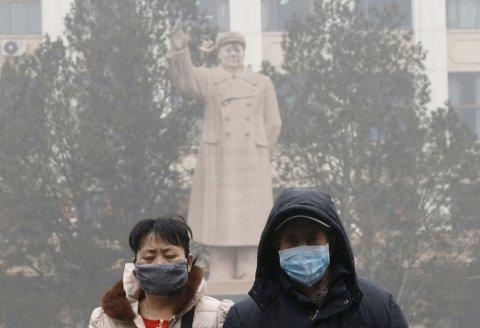 BRUKER MASKE: En statue av Folkerepublikken Kinas største kommunistleder Mao Zedong hilser innbyggere i Beijing på vei gjennom forurenset smog. Det er nå blitt vanskelig å få tak i maskene, ble det meldt onsdag. Foto: Reuters / NTB scanpix