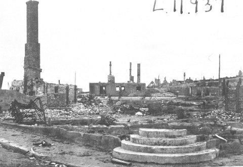 EN BY I RUINER: Slik så Kirkenes ut etter tyskernes tilbaketrekning, med hus i ruiner og skorsteinspiper som stikker opp mot himmelen. Bildet er tatt i sentrum av byen. Ødeleggelsen var total. Bare 28 hus sto igjen.