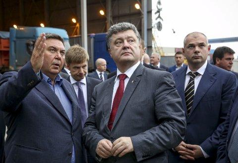 VINNER: Blokken som støtter Ukrainas president Petro Porosjenko (i midten), ser ut til å vinne søndagens valg til ny nasjonalforsamling i landet.