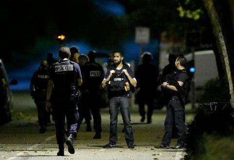 AKSJONERTE: Fransk politi under aksjonen i Boussy-Saint-Antoine nær Paris, torsdag kveld. Tre unge kvinner ble pågrepet og en av dem ble skutt og skadd under aksjonen.