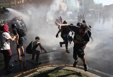 SAMMENSTØT: Opprørspoliti møtte demonstranter med vannkanoner i Santiago i Chile mandag.