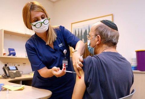 En israelsk mann får sin tredje Pfizer-dose på en klinikk utenfor Tel Aviv i Israel.