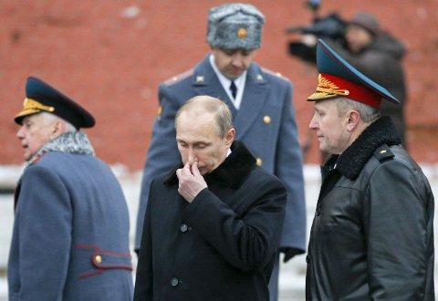 Russlands president Vladimir Putin (i midten) fotografert søndag under en seremoni for å markere Dagen for forsvar av fedrelandet ved Den ukjente soldats grav ved muren til Kreml.