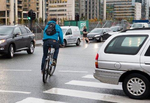 Ruter vil gi gratisbilletter til folk som sykler i rushtiden. Illustrasjonsfoto: Syklist mellom biler ved Langkaia og Operaveien (2015).