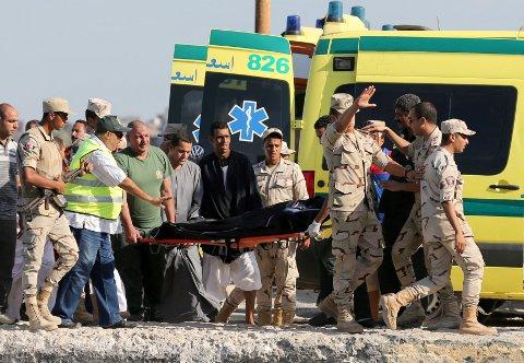 OMKOMMET. Redningsmannskaper bærer bort en av de omkomne etter et båtforlis utenfor Egypt.