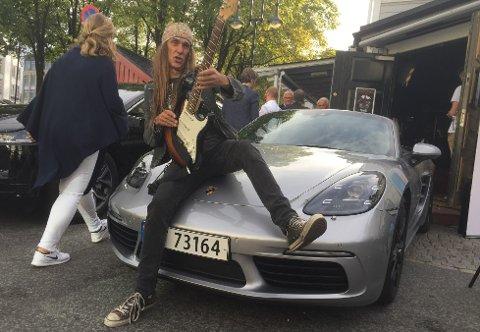 Ronni Le Tekrø med el-gitar og Porsche i Arendal. Til venstre skimter vi forøvrig en Jaguar Ipace. Elbilene er ikke som de var.