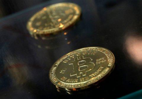 Symbolske bitcoin-mynter plassert på en tellemaskin i Hongkong. Foto: Kin Cheung / AP / NTB scanpix