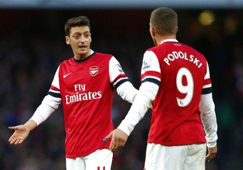 Arsenals Mesut Özil (t.v.) og Lukas Podolski diskuterer under en kamp mellom Arsenal og Crystal Palace i London 2. februar 2014.