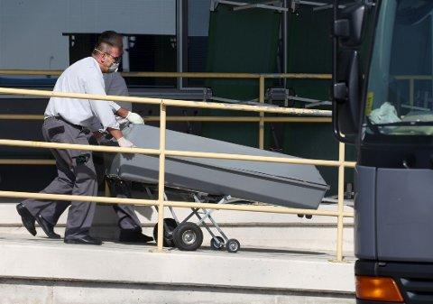 En av kistene bringes om bord i en kjølebil i landsbyen Nickelsdorf fredag. Torsdag ble det funnet en parkert lastebil på en motorvei med 71 døde flyktninger i lasterommet.