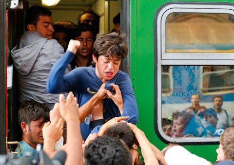 Kaos på stasjonen Keleti-stasjonen torsdag da mange migranter forsøkte å ta seg om bord i dette toget. Over 150.000 migranter har kommet til Ungarn i år, de fleste kommer over grensen fra Serbia.