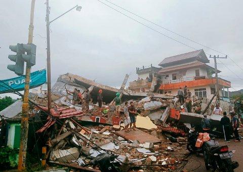 Innbyggere i Mamuju på Sulawesi i Indonesia ved en sammenrast bygning etter jordskjelvet fredag. Foto: Rudy Akdyaksyah / AP / NTB
