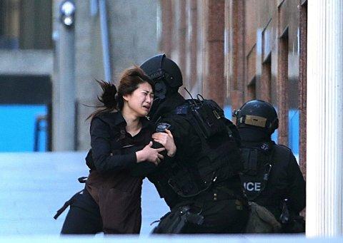 I SIKKERHET: Et gissel løper i sikkerhet til politiet som venter utenfor kafeen.