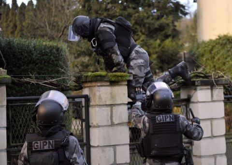 TUSENVIS I AKSJON: Politifolk fra spesialstyrken GIPN i aksjon i landsbyen Corcy torsdag ettermiddag. Titalls tusen politimenn og militære deltar i jakten på de to mennene.