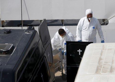 BÆRES I LAND: Personell fra den italienske kystvakten bærer likene av båtflyktninger inn til havnen i Malta.