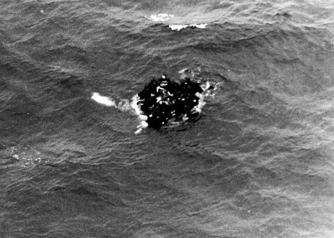 Overlevende klamrer seg til en livbåt etter ulykken der Komsomolets gikk ned sørvest for Bjørnøya i 1989. Foto: Luftforsvaret / NTB