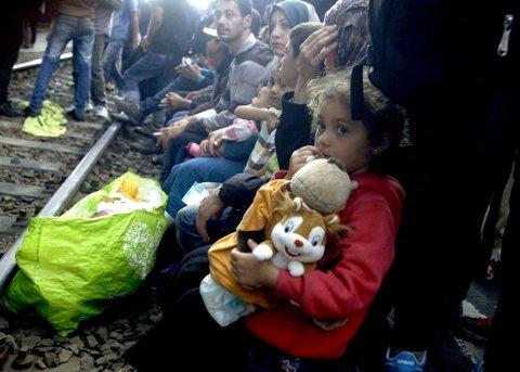 Migranter venter ved jernbanesporet på stasjonen Keleti i Budapest torsdag.
