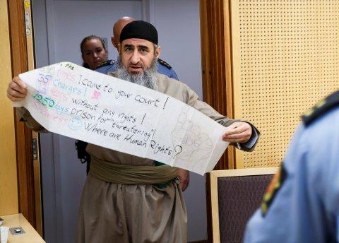 Krekar med en håndskreven plakat ankommer Oslo tingrett mandag. Han er tiltalt for oppfordring til straffbare handlinger i forbindelse med et NRK-intervju Foto: Heiko Junge / NTB scanpix