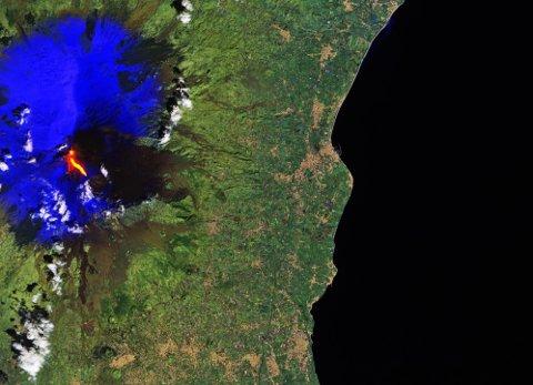 Dette bildet fra den europeiske romfartsorganisasjonen ESA viser hvordan lavaen flyter ned fra vulkanen Etna på Sicilia torsdag. Blåfargen viser snøen på fjellet.