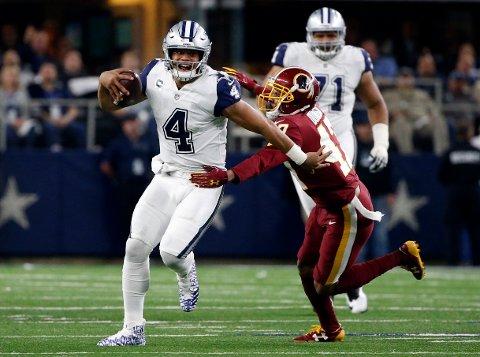 Quinton Dunbar prøver å takle Dallas Cowboys-quarterback Dak Prescott i en NFL-kamp. Dunbar er siktet for et væpnet ran begått onsdag. Rett før politiet utstedte pågripelsesordre snakket han i en pressekonferanse om at han ville takke sin nye klubb for tilliten med eksemplarisk oppførsel. Foto: Ron Jenkins, AP / NTB scanpix