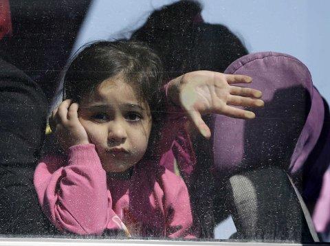 TIL FASTLANDET: En jente kikker ut av bussvinduet idet hun akommer havnebyen Elefsina sammen med andre migranter og flyktninger etter reisen fra Lesvos mandag. Mandag oppgis det å være 50.000 migranter og flyktninger som er strandet i Hellas.