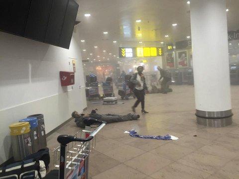 En skadd mann ligger på gulvet etter eksplosjonene på Zaventem flyplass nær Brussel tirsdag.