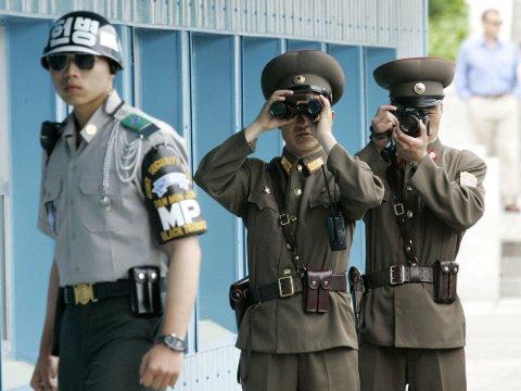 En sørkoreansk soldat (til venstre) og to nordkoreanske soldater avbildet i den demilitariserte sonen langs grensen mellom Nord-Korea og Sør-Korea.