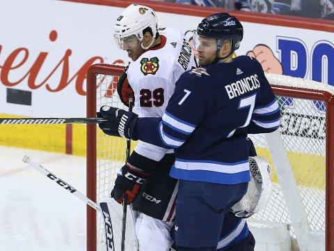 LIGGER FORAN: Andreas Martinsen (hvit drakt) og Rockford IceHogs slo Manitoba Moose i AHL-sluttspillet natt til lørdag. Her i duell med Ben Chiarot fra en tidligere kamp i Winnipeg.