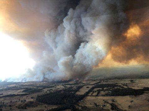 KRAFTIGE SKOGBRANNER: Røyk fra skogbrannen i Burchan i delstaten Victoria stiger høyt til værs på dette bildet tatt 30. desember. Myndighetene jobber nå med å få oversikt over skadene.