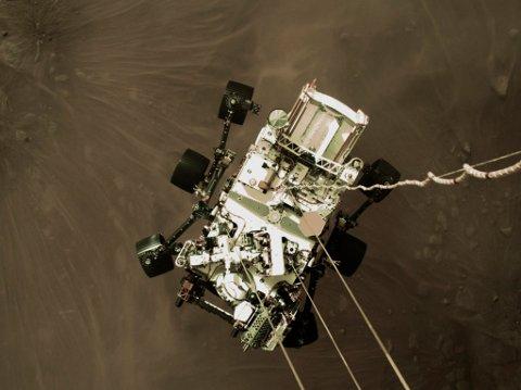 Nasa-roveren Perseverance henger like over Mars-overflaten, bare øyeblikk før landingen torsdag. Foto: Nasa / AP / NTB