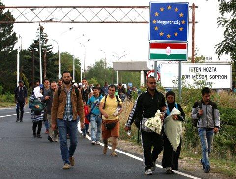 KRYSSER GRENSEN: Migranter på vei over grensen mellom Ungarn og Østerrike ved Nickelsdorf torsdag.