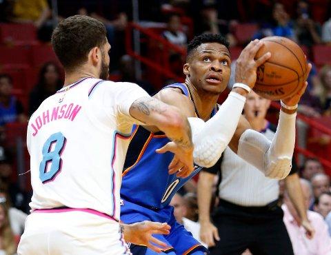 Russell Westbrook (til h.) noterte trippel-tosifret da Oklahoma City Thunder var ett av tre lag som sikret sluttspillplass i NBA mandag. Her leter han etter en skuddmulighet mot Miami Heat-spiller Tyler Johnson. Foto: Wilfredo Lee, AP / NTB scanpix