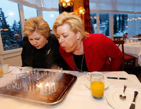 LYKKELIGERE DAGER: Statsminister Erna Solberg og Frp-leder og finansminister Siv Jensen blåser ut lys for å feire 100 dager i regjering i sveitsiske Davos i januar 2014.