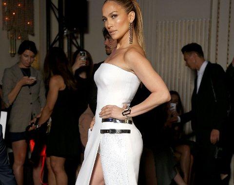 JENNIFER LOPEZ kom til Atelier Versaces visning i et antrekk som var en blanding mellom en kjole og en buksedress.