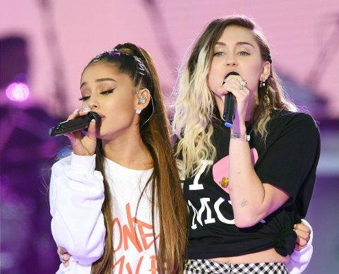 Ariana Grande (til venstre) og Miley Cyrus under One Love Manchester-konserten søndag kveld.