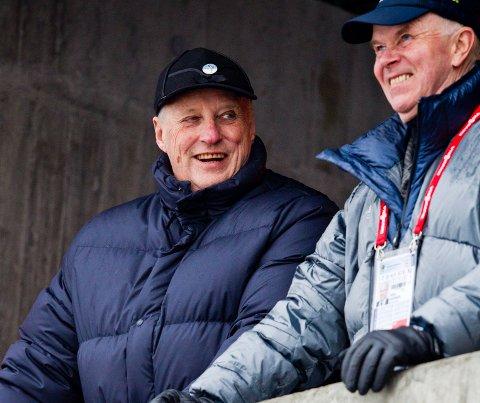 KONGETRIBUNEN: Kong Harald med IBU-president Anders Besseberg (t.h.) før kvinnenes 10 km jaktstart i verdenscupen i skiskyting i Holmenkollen i 2014.