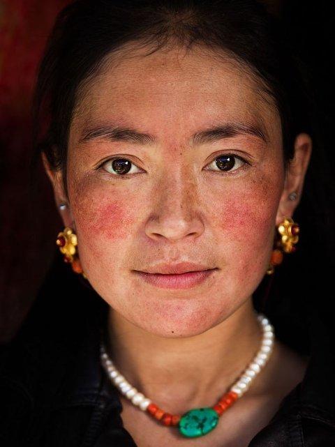 """Sichuan, Kina: Blant de mest grasiøse kvinnene Noroc har møtt er denne tibetanske tobarnsmoren i en avsidesliggende landsby. Slik så hun ut da hun åpnet døren; hun hadde nettopp ryddet huset, men hadde likevel på seg smykkene sine. """"Jeg fant at tibetanske kvinner kler seg med stil i alle livets øyeblikk"""", skriver Noroc."""