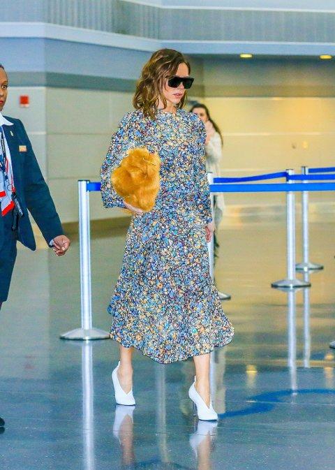 ROMANTISK: Victoria Beckham er romantisk kledt i denne blomstrede kjolen, men legg merke til clutch-veska i fake fur.