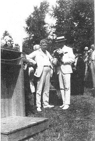 Doktor Christensen overrekker blomster og gratulerer Roald Amundsen etter hjemkomst fra en av sine ekspedisjoner. Amundsen var pasient hos dr. Christensen.
