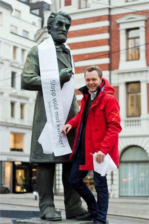 Kampanjeleder i Hvitt Bånd Gjermund Skaar tester ut et hvitt bånd på statuen av Johan Sverdrup (statsminister 1884 – 1889).