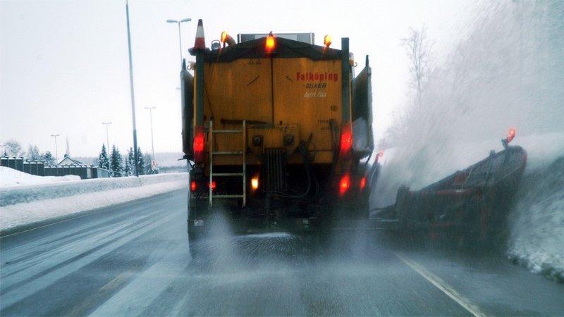 Lastebil kjører på veien. Salter veien. Snø på sidene av veien.