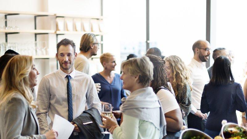 Gruppe mennesker som mingler i jobbsammenheng